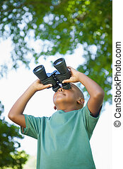 Little boy looking up through binoculars in the park on a...
