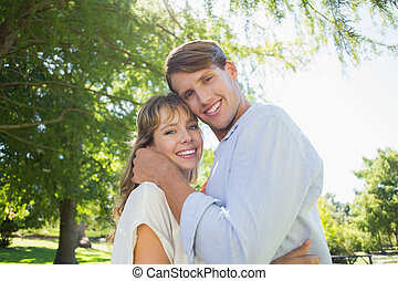 Cute couple hugging and smiling at camera in the park
