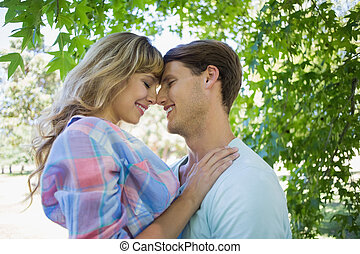 Cute couple smiling and hugging in the park on a sunny day