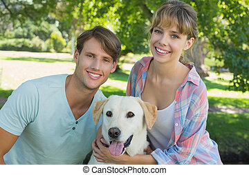 Happy couple sitting with their labrador in the park smiling...