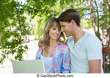 Smiling young couple sitting on park bench using laptop