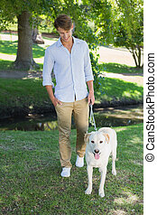 Handsome smiling man walking his labrador in the park on a...