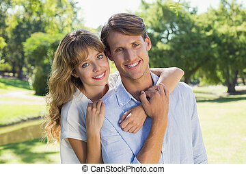 Cute couple smiling at camera together in the park