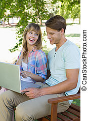 Cute young couple sitting on park bench using laptop