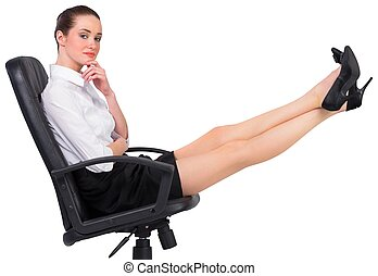 Businesswoman sitting on swivel chair with feet up on white...