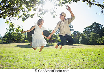 Cute couple jumping in the park together holding hands on a...