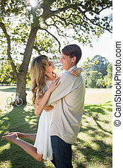 Smiling couple embracing in park