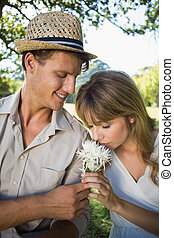 Smiling man offering his girlfriend a white flower in the...