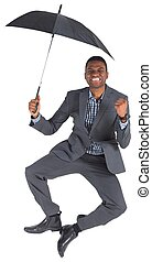 Businessman cheering and holding umbrella on white...