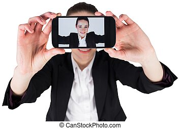 Businesswoman taking a selfie on smartphone on white...
