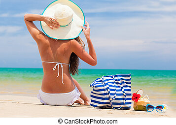 back view of a woman in bikini and straw hat with beach bag...