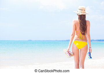 young beautiful woman in yellow bikini and straw sun hat...