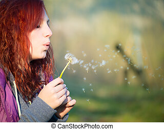 young teenager girl with red hairs blow to dandelion flower