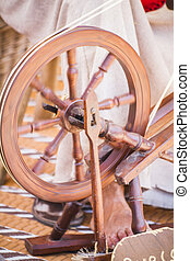 distaff, woman spinning yarn on an old spinning wheel