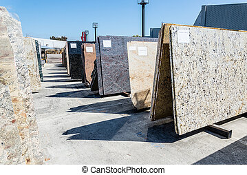 Colorful granite slabs for sale in store yard