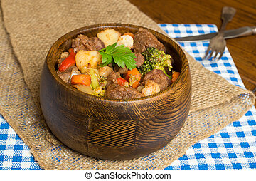 beef stew - Hearty beef stew in wooden bowl