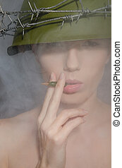 Portrait of woman in fog with a helmet and  cigarette-bullet
