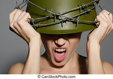 Woman in army helmet with barbed wire isolated on gray
