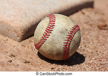 Baseball and Base - A baseball sits next to a dusty wellworn...