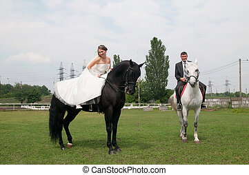 bride and groom sitting on a horse, meadow, nature