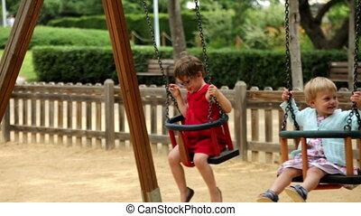 Laughing girls on swing