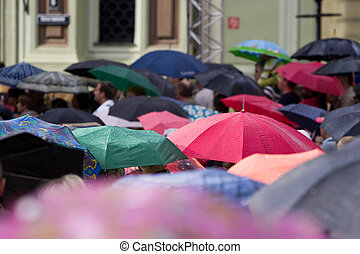 Crowd of people with umbrellas - Busy street with crowd of...