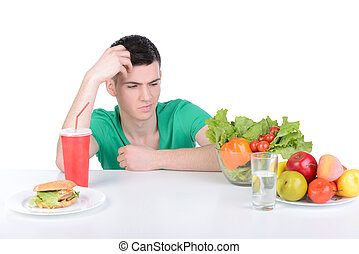 Fast Food - Young man holding in front a bowl of salad and a...