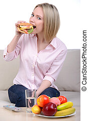 Fast Food - Woman making decision between healthy food and...