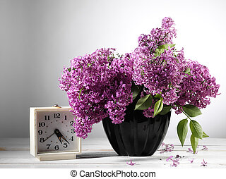 lilac flower on table with alarm clock