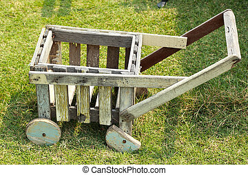 Wooden trolley for gardening on green grass.