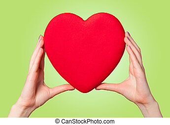 Hands holding shape heart on green background.