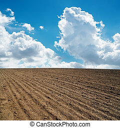 clouds in blue sky and plowed field