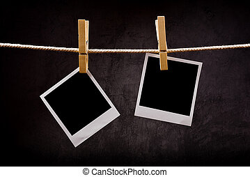 Photography paper with instant photo frames attached to rope with clothes pins. Copy space for your image.