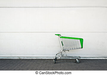Empty Shopping Cart parked in front of large supermarket....