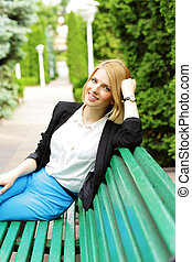 Cheerful woman sitting on the wooden bench