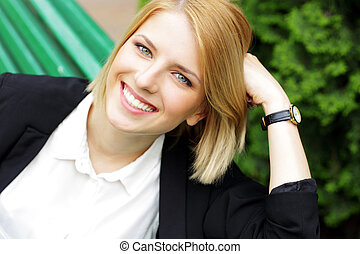 Happy woman sitting on the wooden bench