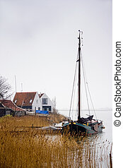 Fishing boat at the lake in winter - Fishing village and...