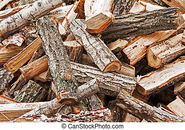 Dry chopped firewood logs in pile. Nature background.