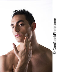 Handsome young man applying moisturizing cream on his faces...