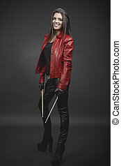 Portrait of young smiling brunette musician woman with drumsticks against grey background