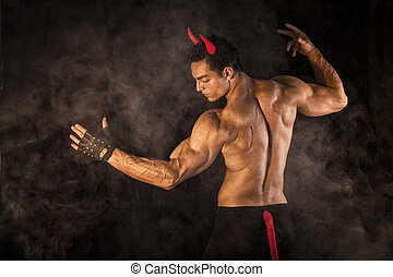 Shirtless muscular male bodybuilder dressed with devil...