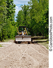 large yellow grader resurfacing a narrow rural road