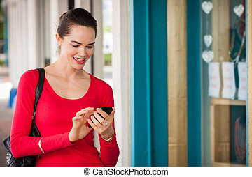 Smiling woman texting on mobile phone - Smiling beautiful...