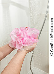photo of woman lathering pink sponge at shower - Closeup...