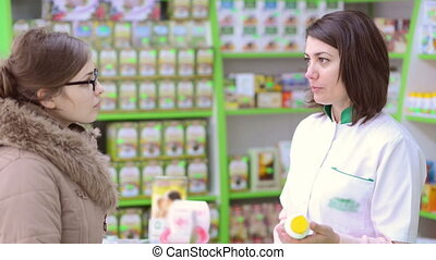 Drugstore Customer - Young female pharmacist in a drugstore...