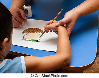 Childs hand with a brush for drawing - Hand of a woman helps...