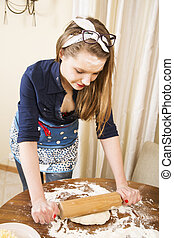 Woman at sexy suit make dough flatly with pin