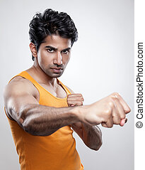 Giving a knockout punch - Handsome Indian man giving a...