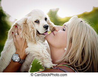 Woman playing with dog - Beautiful young blonde woman is...