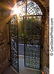 Old gate - Sun shining through the bars of a wrought-iron...